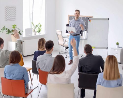 Male business trainer giving lecture in office